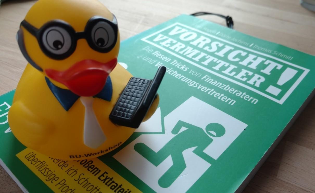 Ente mit Laptop auf dem Buch Vorsicht Vermittler